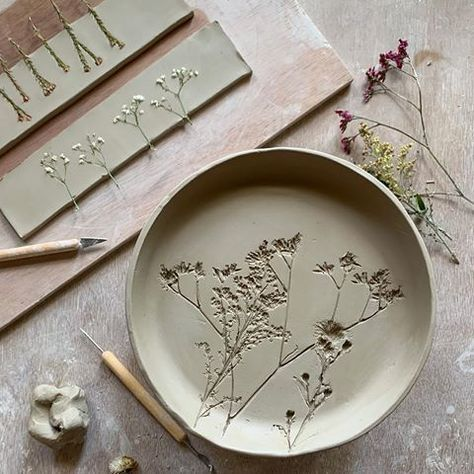 Clay pottery plates imprinted with dried flowers.