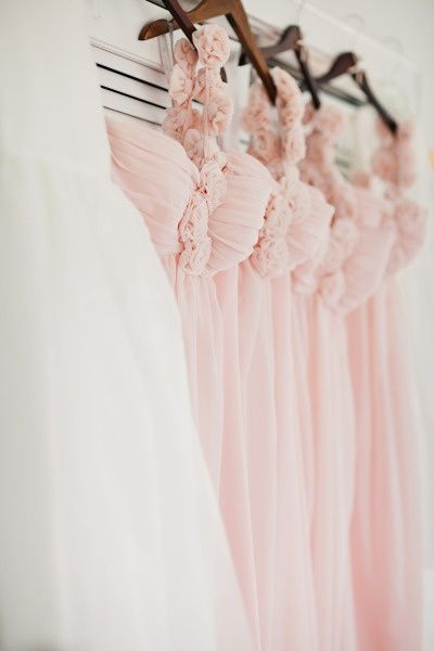 bridesmaid dresses hanging next to the bride's dress
