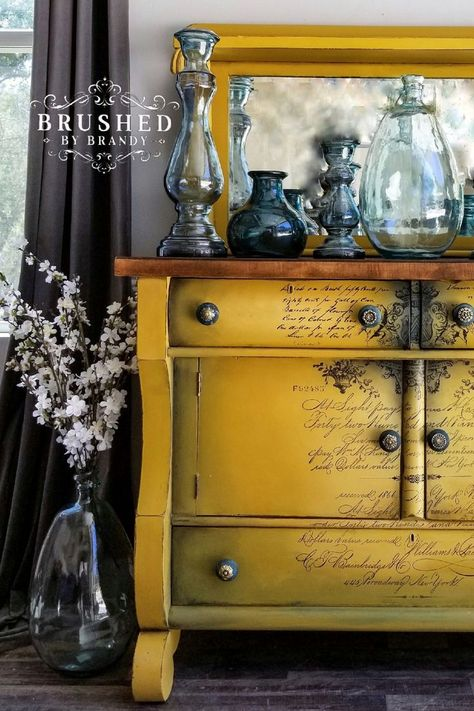 This empire style sideboard was cleaned with white lightning, and coated in clear Boss to prevent bleeding. Then painted in colonel mustard and shaded with collard greens and stormy seas. I used a Parisian letter transfer down the center and added moulds to the original wood knobs and painted them with Bronze patina with blue spray. #brushedbybrandy #blendlikebrandy #paintblending | Mustard Empire Sideboard | Learn How to Paint Furniture | Furniture Painting Ideas | Script Furniture Transfer |