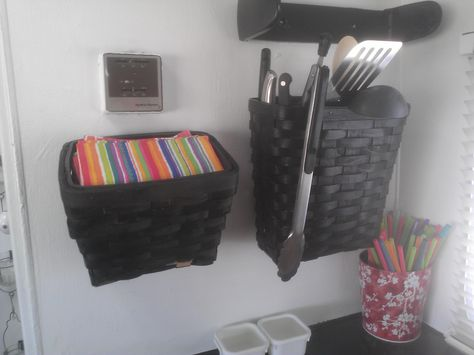 Inexpensive spraypainted baskets mounted on wall for cooking utensils, knives, napkins, potholders, etc.