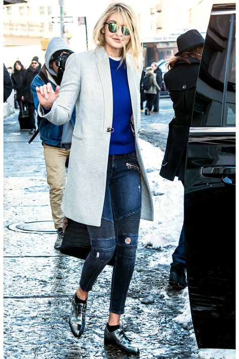 Love the coat! Gigi Hadid wearing a long grey coat, cobalt crew neck sweater, cropped skinny jeans with textured striped along the knees and distressed areas throughout, and metallic pointed-toe shoes