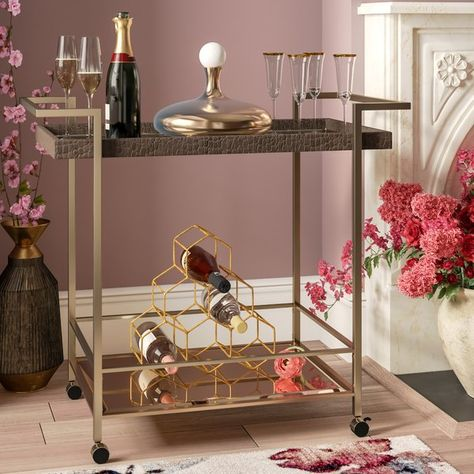 This Wine / Serving Cart is incredibly stylish with a bronze glass top and uniquely bent champagne metal legs to provide not only a sturdy base but bring a unique feel to your home. This Wine / Serving Cart's art deco design has the power to effortlessly update any room it is placed in. Four casters offer easy mobility. Keeping this piece looking good as new has never been easier due to its metal and glass construction. Simply run a damp cloth over the surface to make it as good as new.