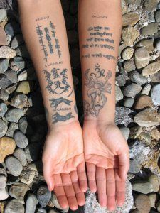 The tattoos on the inner arms: 3 Incan Laws inscribed along with several other ancient scriptures, mantras and symbols.