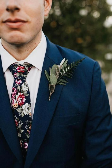 navy blue groom attire with floral tie and boutonniere / Navy Blue and Greenery Wedding Color Ideas
