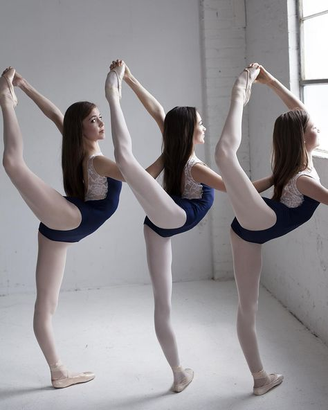 Dance photography captures three ballerinas stretching for ballet class in their…