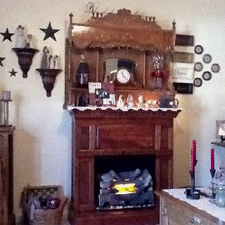 The top of my in-laws antique pump organ repurposed on top of my little fireplace. Couldn't use the organ since I have my Grandma's but this way I can appreciate their's.