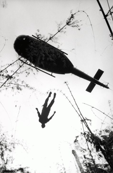 The body of an American paratrooper killed in action in the jungle near the Cambodian border is raised up to an evacuation helicopter in Vie...