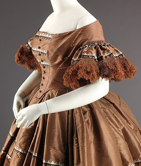1858-1859 dress with densely gathered sleeve flounces with fringe and two-flounced skirt, triple box pleated at the waist. Via the MET. #Victorian #fashion #dresses #brown