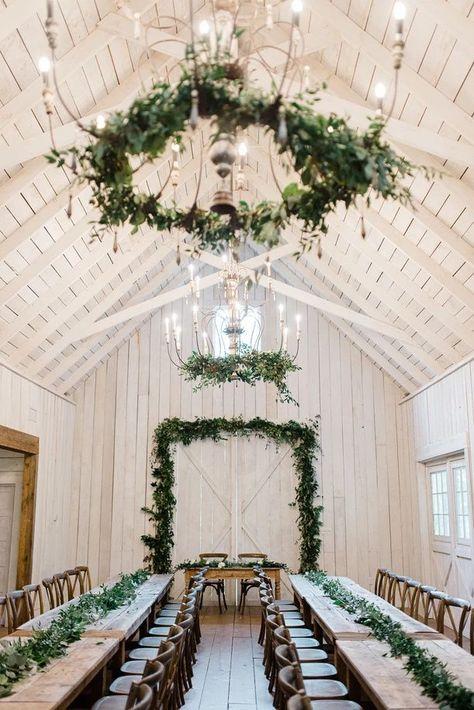 Greenery garland tablescape and hanging installation in a rustic barn! #echoesofeden #echoesofedneflorals #nashvilleweddings #nashvilleflorist #nashvillevenues #greenerygarland #tablescape #hanginggreenery #rusticbarn #tnbride