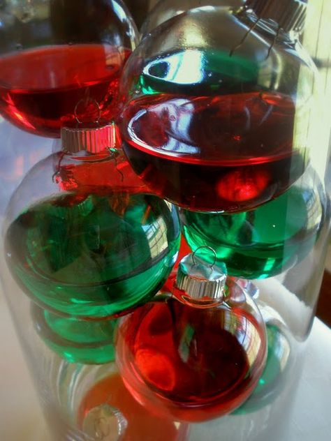 clear ornaments with colored water stacked in a vase