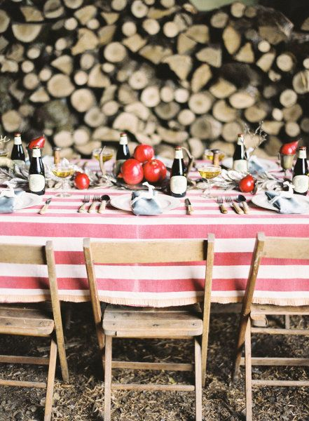 table setting. wood back drop, pomegranates, powder blue napkins, and striped table cloth.
