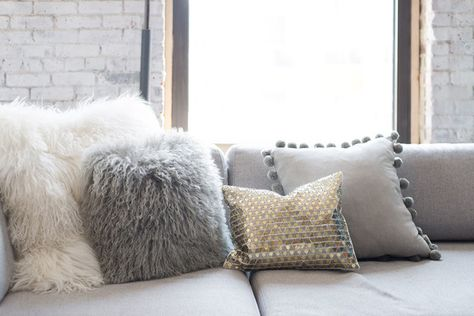 A collection of neutral and metallic throw pillows soften the industrial space's exposed bricks and beams.