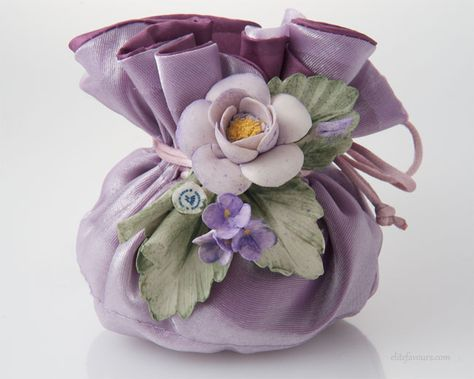 Double layer silk sachet filled with Jordan Almond candies and soft filling, hand made Capodimonte ceramic flower composition.