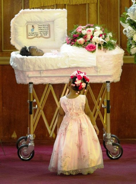 Sad beyond words: The body of Londyn Samuels, lies in a casket as her sister, Paris, looks up at her during the funeral at New Hope Baptist Church in New Orleans on Saturday, September Samuels was murdered while in the arms of her babysitter.