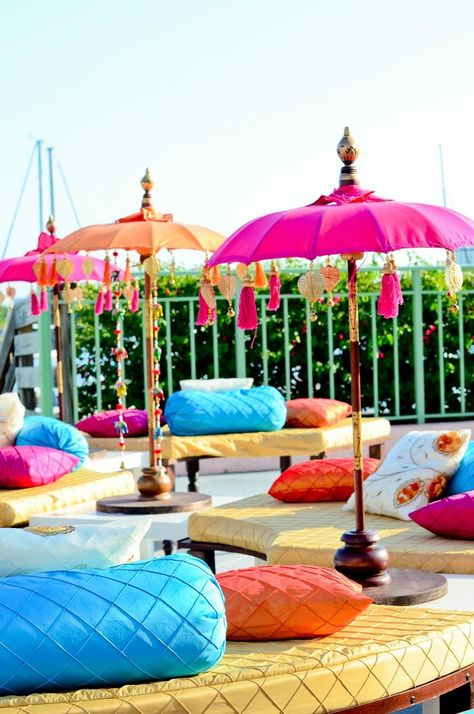 Lounge seating with lots of plush pillows is perfect for a mehndi party. If your event is outdoors, add a burst of color with umbrellas that match the decor. | via Suhaag Garden