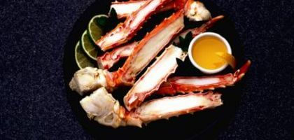 Slice cooked crab legs open horizontally along the leg for easy access to the meat.