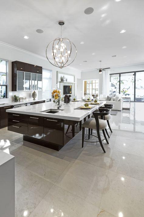 Large modern white and dark brown kitchen with huge modern island with breakfast bar.