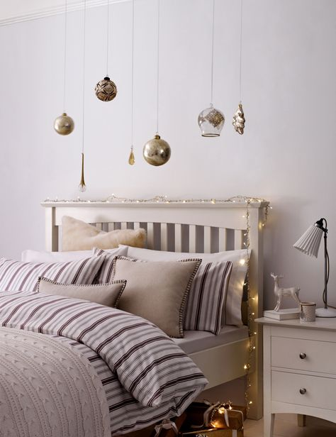 Don't forget your bedroom! Add Christmas cheer with sparkling fairy lights and decorative baubles.