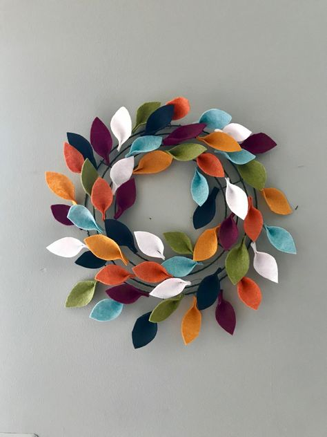 It takes more time than talent to create, so keep reading to find out how to make your own felt leaf wreath. It's a colorful addition to any Fall decor. Felt Flower Wreaths, Felt Wreath, Wreath Crafts, Diy Wreath, Felt Flowers, Wreath Making, Autumn Crafts, Holiday Crafts, Fall Felt Crafts