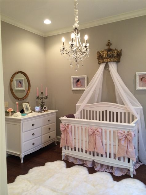"Eva's elegant nursery. Antique mirror, linens and drapery from Restoration Hardware. Octo sheepskin rug, chandelier, ivory dupioni silk chandelier cord cover, 3 large dupioni silk crib bows from Caty's Cribs on Etsy. Baby girl nursery. Soft pink accents against gray walls (SW ""anew gray"") with BM ""white chocolate"" trim."
