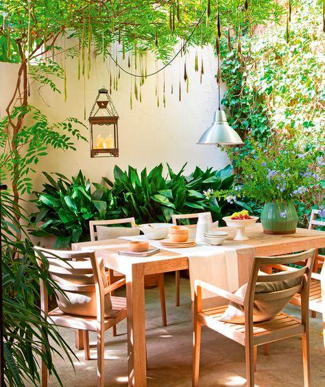 Patio comedor con mesa y sillas de madera, plantas colgantes, camino de mesa, farol y lámpara de techo de metal