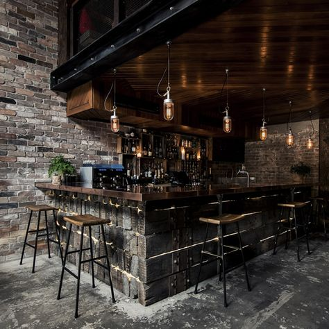 The bar downstairs is made of reclaimed railway sleepers that have been lashed together with ratchet straps, and it's topped with a lovely polished copper top that zings against the weathered wood. A mezzanine level set back from the entrance opens up the space to its full cavernous effect...