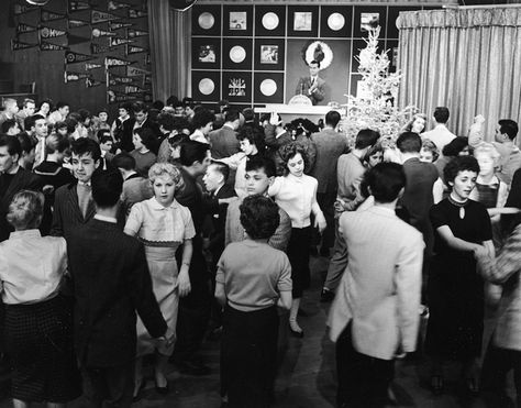 A dance or a sock hop in the 1950's with a d.j. playing records, boys in jackets and white shirts, girls in sweaters or blouses with skirts.