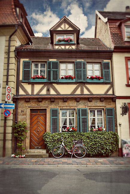 Quaint house in Bamberg, Germany with a bicycle out front and decorative flowers in the windowsills.© John Bragg Photography