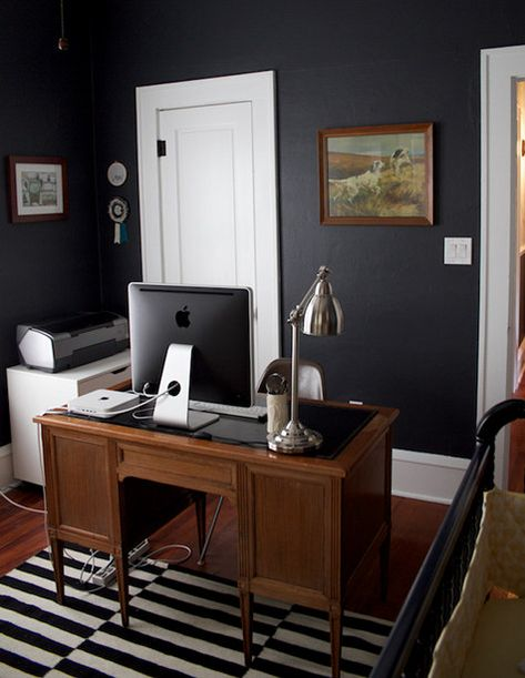 Charcoal walls with white trim and doors and wood tones.