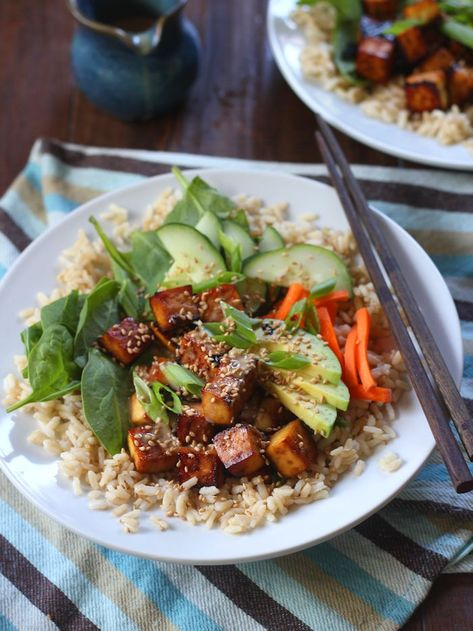 Tofu cubes are soaked in a savory ginger-sesame marinade and baked until crisp, then served over a bed of rice and veggies topped with wasabi seasoned tahini dressing in these delicious and healthy vegan sushi bowls. #vegan #veganfood #veganrecipes #vegetarian #vegetarianrecipes #meatlessmonday #tofu
