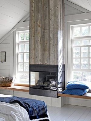 Faced with reclaimed white pine, the gas fireplace's chimney hides a surprise: a flat-screen TV