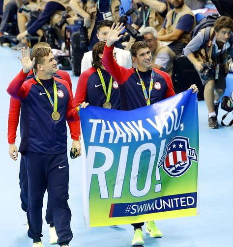 Michael Phelps and Nathan Adrian wave to the crowd while holding a flag with a message that reads 'THANK YOU RIO' as they walk with their teammates...