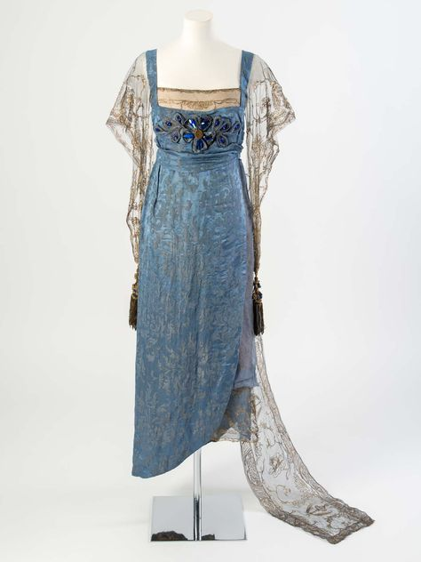 Blue figured silk evening dress with gold net sleeves and train embroidered in gold metal strip and decorated with blue gems and tassels, 1911.Worn by Esme Giffard (née Wallace), daughter of Lucile, to celebrate the Coronation of King George V in 1911 and later altered for a Ball in 1919