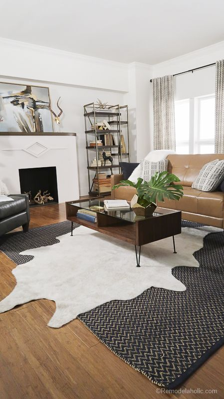 A Living Room Space With A Faux Cowhide Rug Art Nouveau Fireplace And Touches Of Gold Layered Rugs Living Room Cowhide Rug Living Room Rugs In Living Room