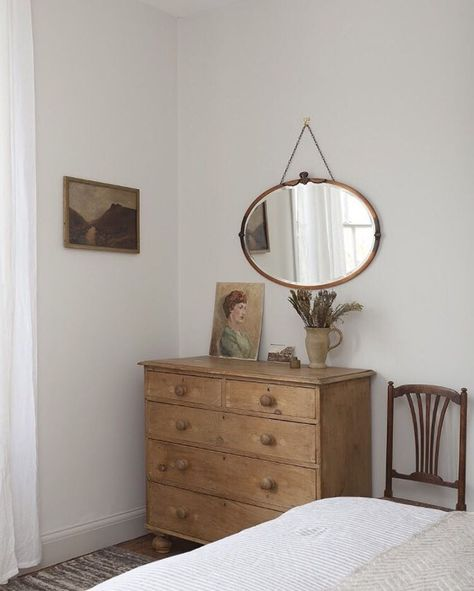 An English pine dresser coupled with accessories in soft colors create a simple and serene bedroom.
