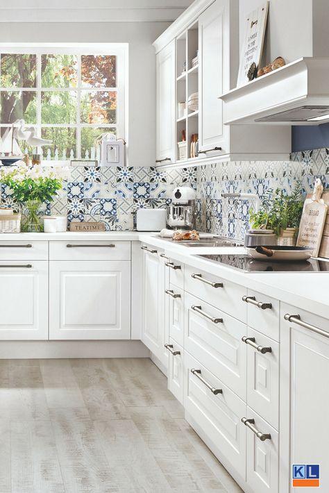 Prachtige witte keuken met achterwand van tegels met een blauw design.