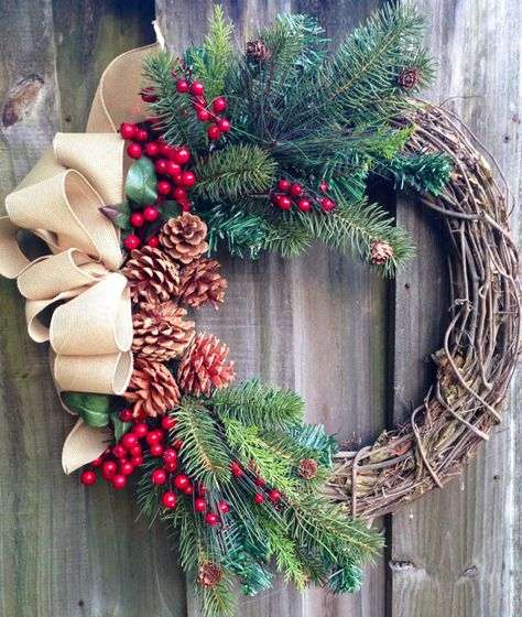 Winter wreath or Christmas wreath using grapevine, red berries, pine, and pine cones with a tan burlap-look bow. on Etsy, $65.00