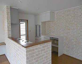 レンガ調のクロスがおしゃれなキッチンまわり リビング側から見えるキッチンファニチャーは白 キッチン側は木目調 キッチンレンガ レストランのデザイン リビング アクセントクロス