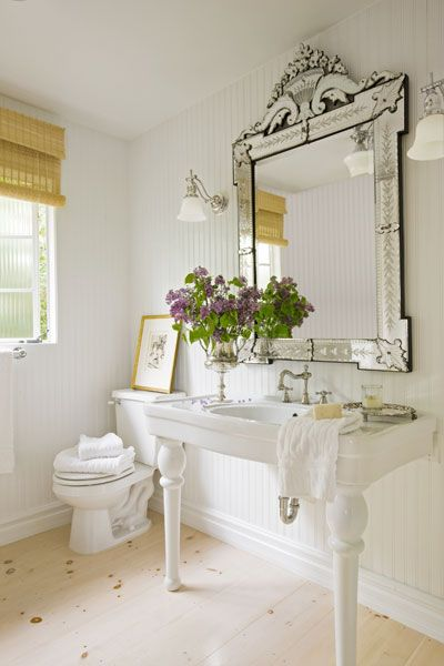 "Powder rooms can suffer from ""builder-basic syndrome,"" with home-center cabinets and minimal mirrors. Go from standard to striking by adding one oversized element, such as a huge mirror. 
