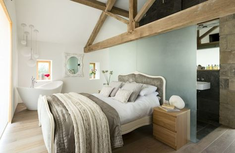 This impressive renovated derelict barn has been transformed by a contemporary interior - not least in this innovative bedroom-cum-bathroom. A modern chandelier suspended above the freestanding bath helps to define the bathing zone.