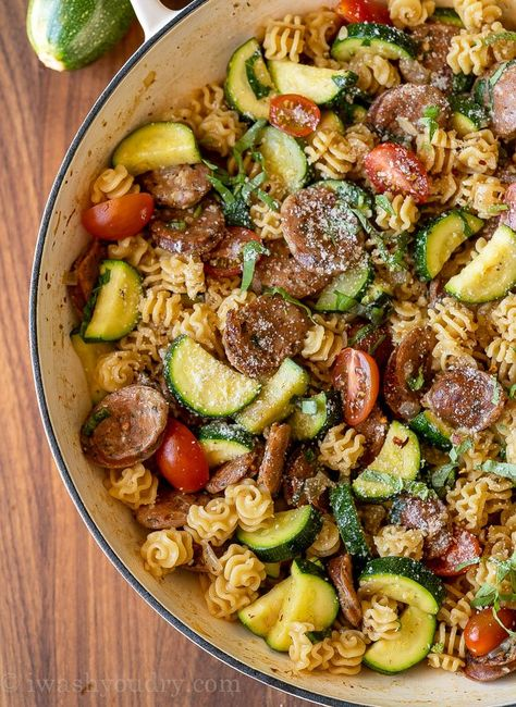 Skillet filled with pasta, sausages, zucchini and tomatoes in a lemon basil sauce.