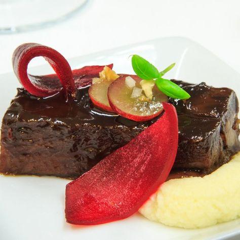 Bœuf braisé au café, purée de chou-fleur au fromage Alfred Le Fermier, pétales d'oignons marinées et garniture de raisins verts et de noisettes