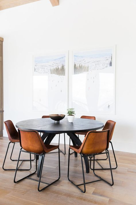 fabulous dining / clean white walls with sexy leather chairs flanking a round mid century modern style table