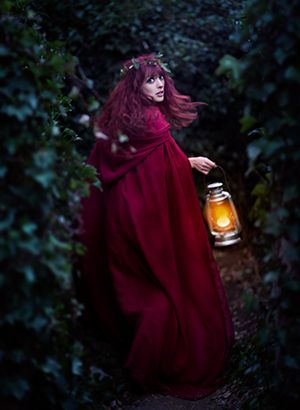 This is a good image of fear in her eyes. A woman in red cape and lantern running though the woods looking over her shoulder