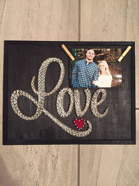The word love is outline in gold nails on a piece of wood that is painted black measuring 14 inches by 11 inches. Two gold clothes pins are attached to hold a 3x5 picture. White string is used for the letters and red string for the small heart. Colors are completely customizable.