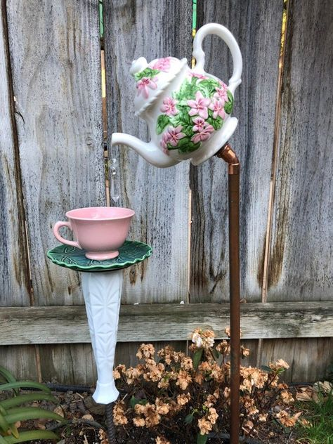 A pretty white tea pot with pink flowers is pouring into an adorable pink tea cup that is sitting on a green leaf saucer. It sits on a 3 ft copper pole and the cup rest on a glass vase that sits on a 2 ft pole. The dangling crystal gives the appearance of tea pouring into the cup. The tea pot is