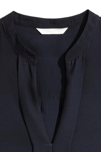 3b05d72d036ea Sleeveless blouse in an airy weave with a small stand-up collar and V-neck  with decorative pleats at the front. Yoke with a pleat at the back and