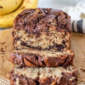 This banana bread is loaded with bananas making it super moist. Nutella swirled into the batter takes this banana bread over the top! #bananabread #bananaandnutella #quickbread #nutella   themarblekitchen.com