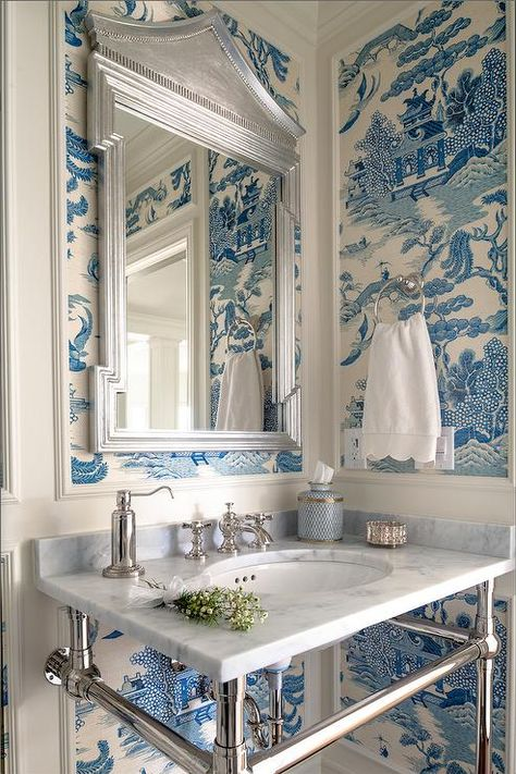 White and blue powder room features walls clad in trim molding framing blue chinoiserie wallpaper lined with a silver pagoda mirror over carrera marble top washstand.