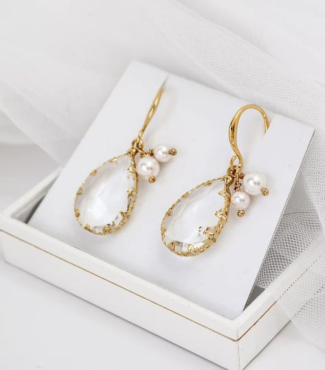 Our Blanca PearlGoldEarrings have a large crystal dropper with two delicate Swarovski Pearls added for a touch of sophistication and elegance to your bridal look. Finished with gold plated wire and ear hook. These would look amazing on both brides and bridesmaids. Visit www.deborahkdesign.co.uk to view our collections. #bridalearrings #crystalearrings #dropperearrings